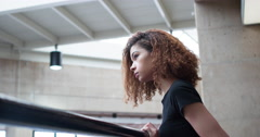 Girl looking into distance leaning on railing 4k Stock Footage