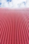 Rooftop of curved red corrugated iron - stock photo