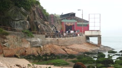 Temple on rocky shore, pathway, people walking, terrace Stock Footage