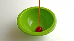 Filling a small green bowl with ketchup - stock footage