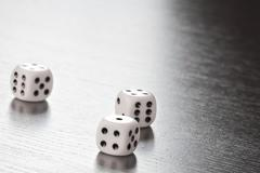 Three white dice on old wood black table with space for text Stock Photos