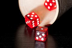 red dice on old wood black table near a container - stock photo