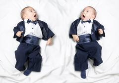 Mirrored photo of cute baby boy wearing an elegant suit with bow tie - stock photo