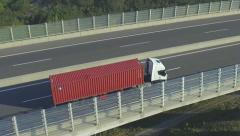 AERIAL: Container truck driving over the highway viaduct Stock Footage