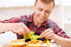 Man adding lettuce leaves  to his sandwich Stock Photos