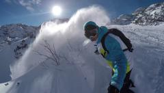 Snowboarder doing powder turns in fresh snow on the mountain - stock footage