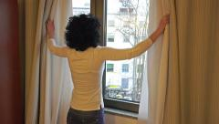 4K Beautiful brunette goes to window and look out concerned for partner Stock Footage