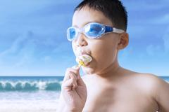 Male kid bites ice cream at seaside Stock Photos