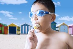 Naked child eating ice cream at coast - stock photo