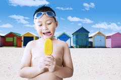 Naked male kid eating ice cream at coast - stock photo