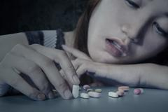 Teenage drug addict with medicine - stock photo