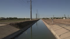 Desert water canal 12 - electrical lines in view Stock Footage