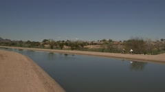 Desert Water Canal 06 with 2 bicycles going by Stock Footage