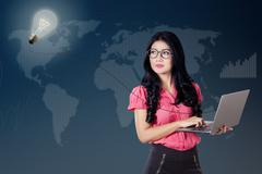 Woman with idea light bulb and laptop - stock photo