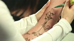 Close-up of mehendi artist draws on model's leg Stock Footage
