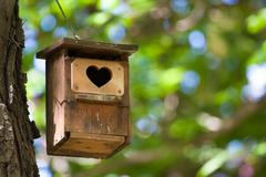Bird house with the heart shapped entrance. - stock photo