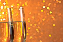 Pair of a champagne flutes on orange and yellow light bokeh background Stock Photos