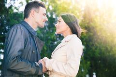 Beautiful couple flirting in park - stock photo