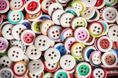Multi colored buttons on a wooden background Stock Photos