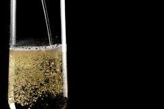 Filling a flute of champagne with golden bubbles Stock Photos