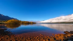 Stock Video Footage of Beautiful Lake Wakatipu Scenery - Low Clouds & Mountain Range. Pan Left