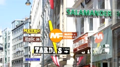Variety of signs of brand shops on a tourist shopping street of Vienna Stock Footage