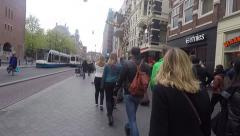 Steady cam Main street walking towards Dam square With people and Tram crossing Stock Footage