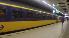 Steady cam People board and exit a train at Schiphol international airport Stock Footage