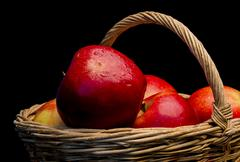 Red apple with drops of moisture in a wicker basket - stock photo