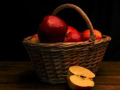 Red apple with drops of moisture in a wicker basket Stock Photos