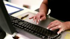 Office typist on computer keyboard, pull focus - stock footage