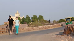 Rickshaw passing down the road, with Jaswant Thada temple in background. Stock Footage