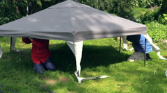 Zoom in father and son fix tent cloth roof on garden arbour Stock Footage