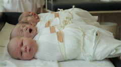 Newborn babies lying on the table at maternity ward, one infant crying. - stock footage