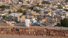 Back view of man sitting on wall watching cityscape. Stock Footage