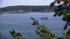 Sailboat motoring between islands - stock footage