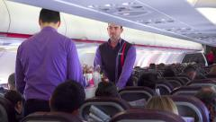 Stewards serve the passengers on plane flight - stock footage