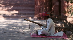 Indian man playing music on string instrument at street in Jodhpur. Stock Footage