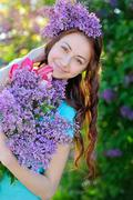 Beautiful girl with a bouquet of lilac walking in spring park Stock Photos