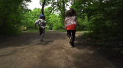two kids running in the park in slow motion - stock footage