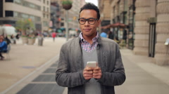 Young African Asian man in city walking texting cell phone slow motion Stock Footage