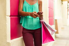African American Girl Sending Text Messaging On Phone Shopping Bags Stock Photos