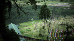 Holy Khecheopalri Lake with prayer flags, long shot Stock Footage
