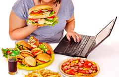 Woman eating junk food Stock Photos