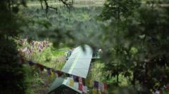 Khecheopalri Lake dock with prayer flags, long shot Stock Footage