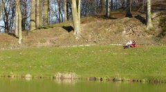 Mature couple relaxing in park next to a pond Stock Footage