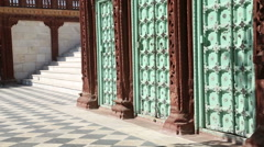 Artistically designed doors by stairs of Jaswant Thada temple, with man passing. Stock Footage