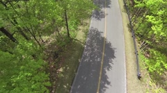 Aerial of Cyclists Racing Along a Forest Road - camera rises into the sky - stock footage