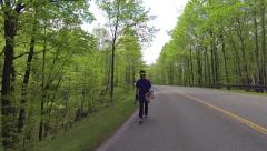 Long boarder walking up the hill with his skateboard Stock Footage