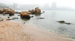 Beach stones in rain, camera move closer, raindrops and foggy horizon Stock Footage